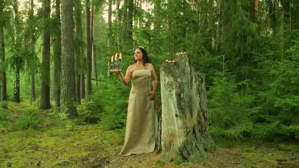 Tajemné lesní víla je připraven velký pahýl se svíčkami a svícny s hořícími svíčkami v ruce drží.