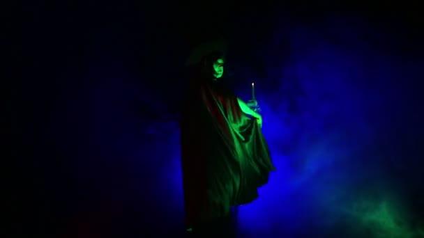 Mladá žena v masce čarodějnice ve světle v kouřové cloně a mávat plášť a kouzelná hůlka