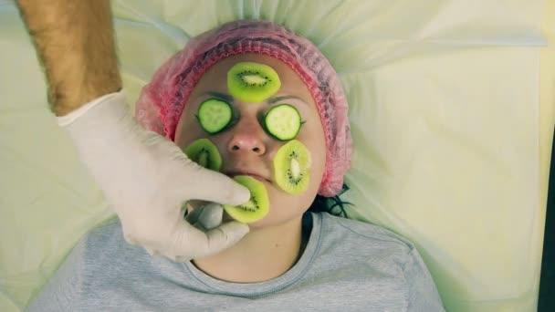 kezében az ember a kozmetikus, a kesztyű eltávolítása egy női arc a maszk, a kiwi és egy uborka