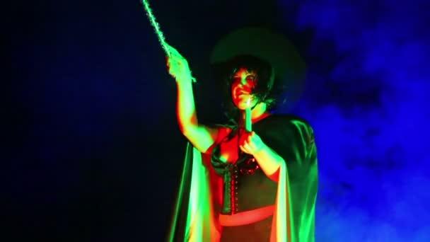 Eine junge Hexe in einem schwarzen Mantel und Hut mit einer Kerze in der Hand in einer Rauchwolke liest Zauber. close-up.