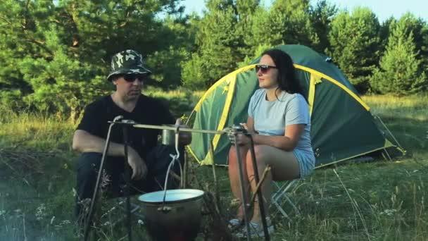 muž a žena turisté jsou sedí u stanu, pití čaje a sledovat hrnci zavěšeném nad ohněm