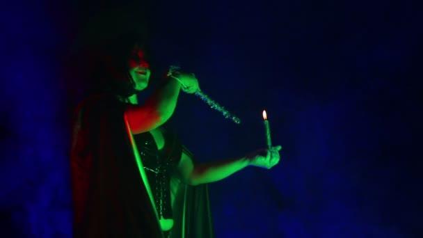 Mladé čarodějnice v černém se svíčkou v ruce v oblaku kouře vyvolává