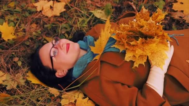 A fű az őszi parkban fekszik, egy fiatal nő, szemüveg és juhar levelei alá tetején rá.