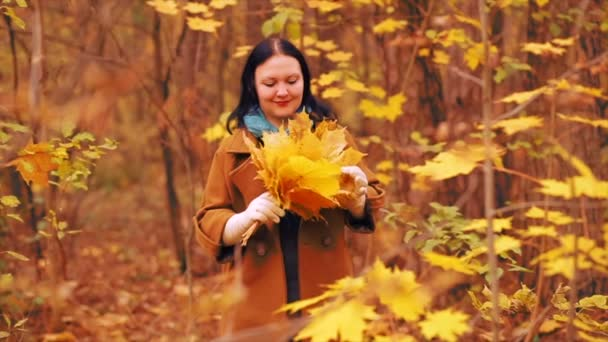 Young brunette woman in a brown coat on a walk in the autumn park with maple leaves in their hands. Slow motion.