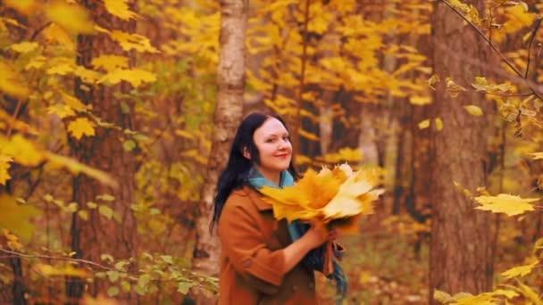 Mladá usměvavá žena v podzimním parku s maple listy v ruce a vrzích
