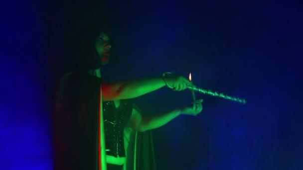 Mladé čarodějnice v černém se svíčkou v ruce v oblaku kouře se zabývá magic s pomocí kouzelného proutku