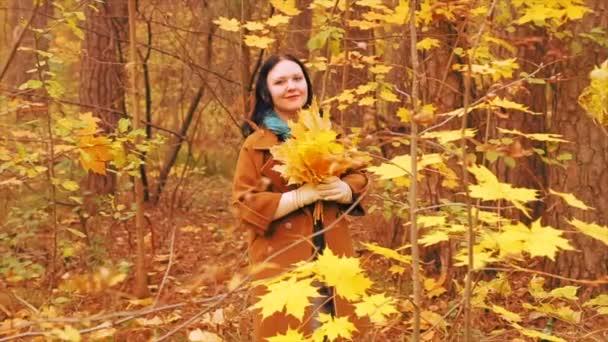 Eine junge Frau, die im Herbstpark spazieren geht, dreht sich mit Ahornblättern in der Hand. Zeitlupe.