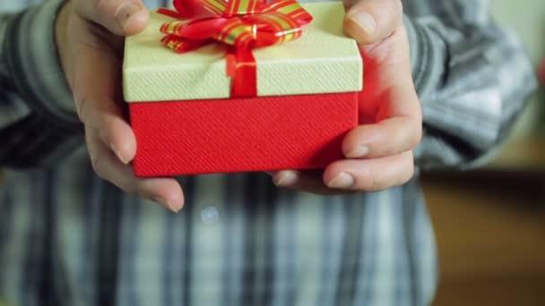 Női kezek üzembe karácsonyi ajándékokat a karácsonyfa alatt. Az átlagos terv.