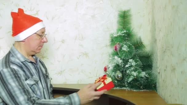 Egy ember, egy Mikulás kalap a napokban karácsonyi ajándékot a család, a karácsonyfa alatt