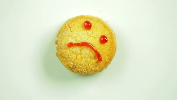Cookies with a funny emoticon drawn by a muzzle emotion sadness. Movement in a circle