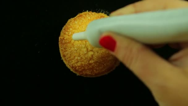A female hand holds a tube of culinary yellow jam and draws funny emoticons on cookies. Time laps. The average plan.