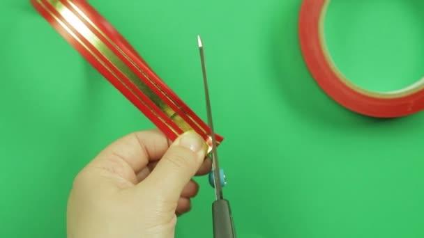 Dámské ruce narovnejte plátky červenou stuhou lukem dárek a dát mu tvar. Zelené pozadí