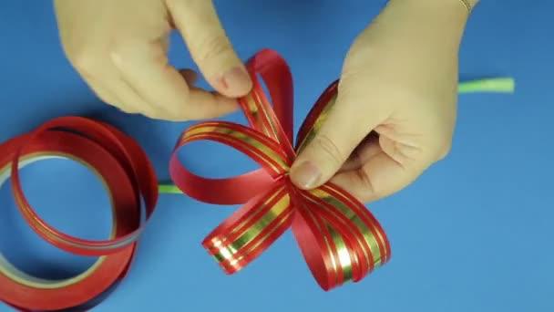 Dámské ruce dávat tvar luk červenou stužkou. Modré pozadí