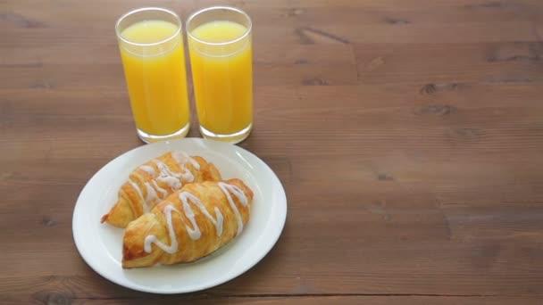 A fából készült asztal két pohár narancslé és egy tányér croissant van. A kamera mozog balról jobbra.