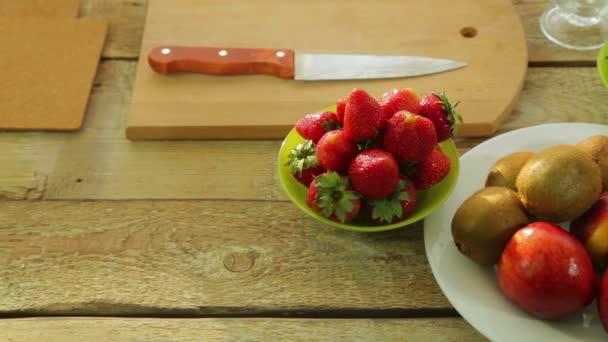 fresh fruit kiwi, peaches, strawberry on a wooden table.