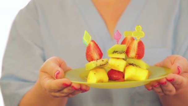 canap friss őszibarack eper és a kiwi gyümölcs zöld női kezek táblán. a kamera mozog jobbra-balra. közeli kép:.