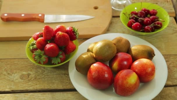 Fresh fruit kiwi, peaches, strawberries and cherries are on a wooden table.
