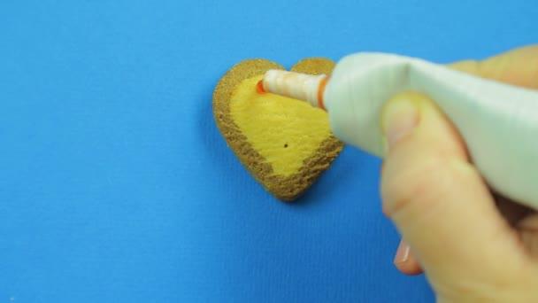 Ženská ruka kreslí zakázal emotikony na sušenky ve tvaru srdce na modrém pozadí