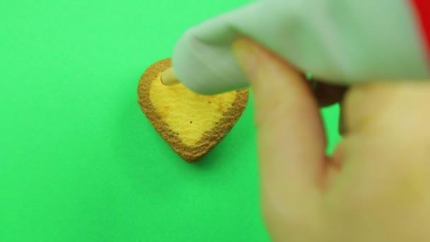 Ženská ruka kreslí cookie ve tvaru srdce na zeleném pozadí s červenou trubici poleva legrační smajlíky