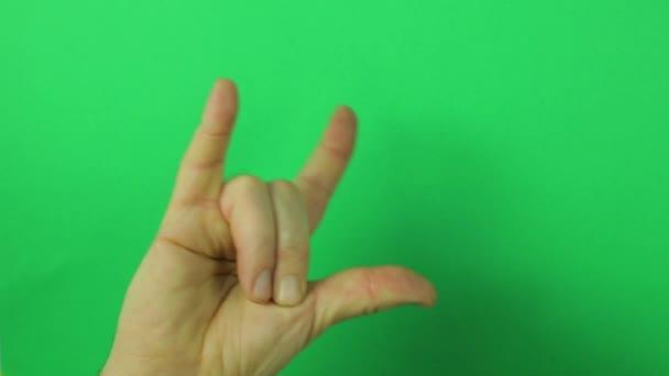 Männerhand auf grünem Hintergrund mit erhobenen Fingern. Nahaufnahme