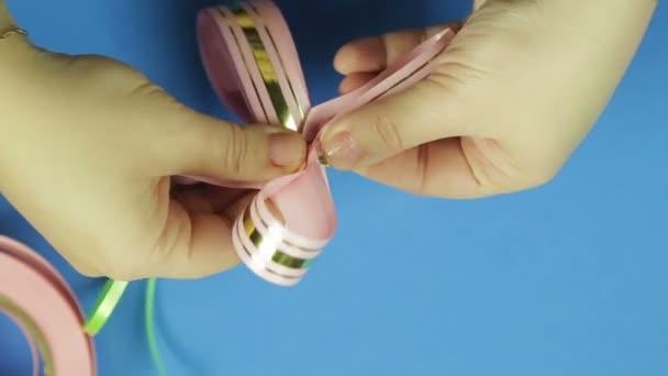 Dámské ruce tvar lístků dar luk růžovou stuhou. Modré pozadí. Ručně vyráběné
