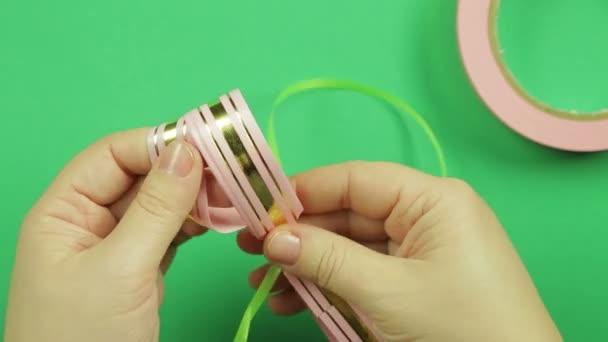 Dámské ruce jsou svázané s zelenou stuhu růžovou stuhou prázdné pro dar luk na zeleném pozadí