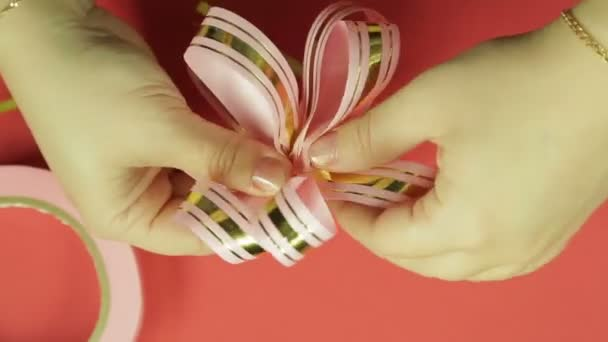 Womens hands straighten the petals of a pink ribbon gift bow and give it the shape of a bow. Red background