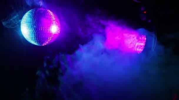 Zrcadlová disko koule na černém pozadí s searchlight paprsky duhové v různých barvách v obláček dýmu