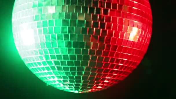 Zrcadlová disko koule na černém pozadí ve světle reflektorů červené a zelené