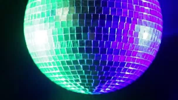 Tükör disco labdát a fekete háttér, kék és zöld spotlámpák fényében. Közeli kép: