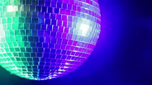 Zrcadlové disco koule na černém pozadí ve světle modré a zelené reflektory