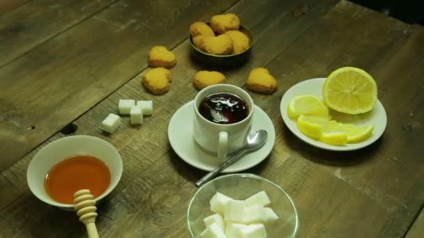 Női kéz darab cukor helyezi egy csésze frissen főzött fekete tea