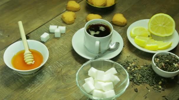 Csésze tea, hegesztés, a méz és a citrom, egy fából készült asztal. Az átlagos terv