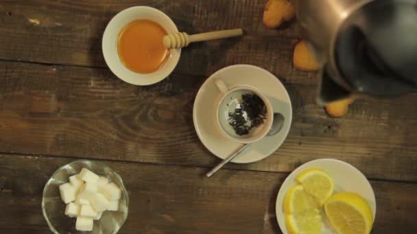 Ženská ruka drží konvici a nalije vařící vodu do šálku pro vaření zelený čaj