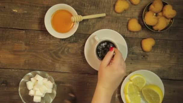 weibliche Hand rührt mit einem Teelöffel in einer weißen Tasse auf einem Holztisch