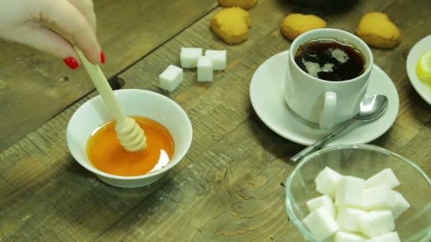 Ženská ruka míchání medu v talířek. Průměrná plán Hd