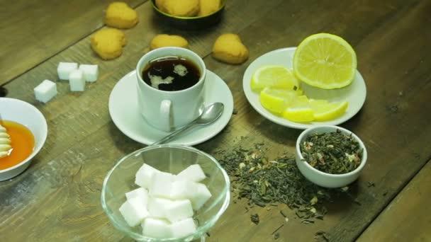 Šálek čaje, svařování, med a citron na dřevěný stůl
