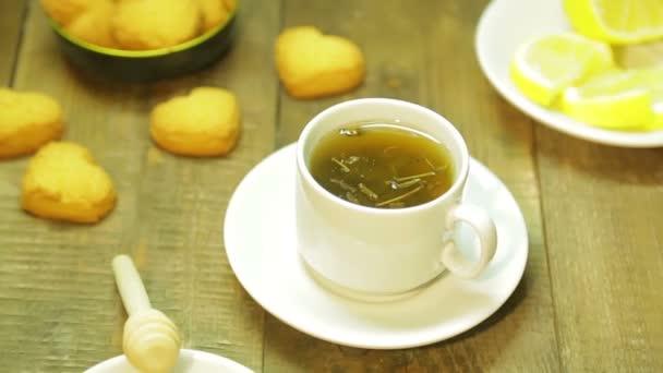 Šálek čerstvě uvařené zeleného čaje na dřevěný stůl. Průměrný plán
