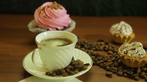 Fehér csészék, sütemény és egy kávé bab az asztalon szétszórt kávé