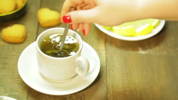 A woman mixes freshly brewed green tea with a spoon in a white cup