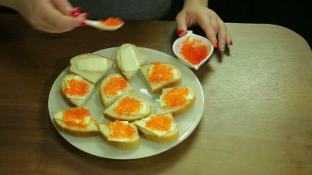 Eine Frau nimmt rote Kaviar aus einem Löffel Iornitsa und breitet sich Butter auf einem Canape mit butter