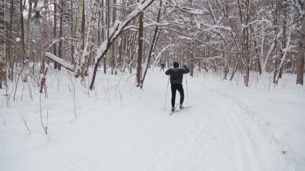 Muži lyžaři jezdí po trati v destinaci winter park