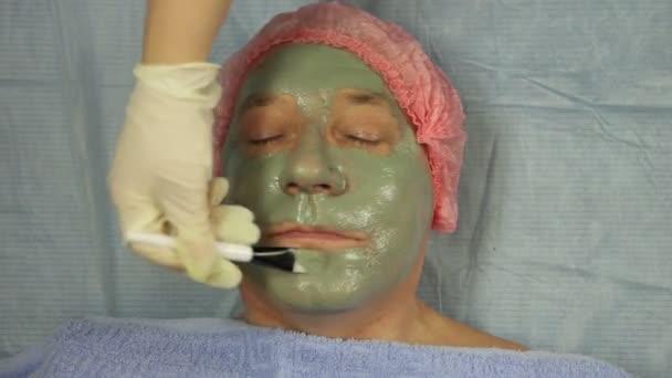 eine Kosmetikerin in Handschuhen trägt einer männlichen Kundin eine Schlammmaske auf