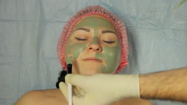 ein männlicher Kosmetiker mit Handschuhen legt einer Kundin eine Schlammmaske mit einer speziellen Bürste auf das Gesicht.