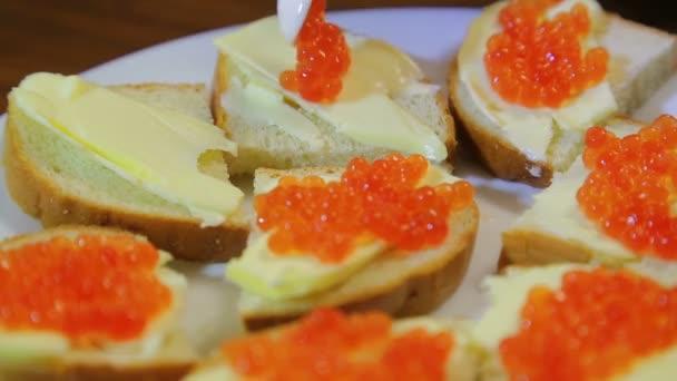 Egy nő, egy evőkanál vajjal canapes kenetet, piros kaviár