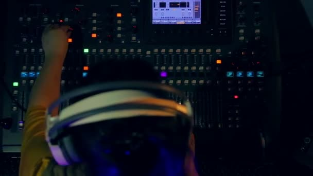 Womans hands on a mixing console mixing tracks for disco in color lighting