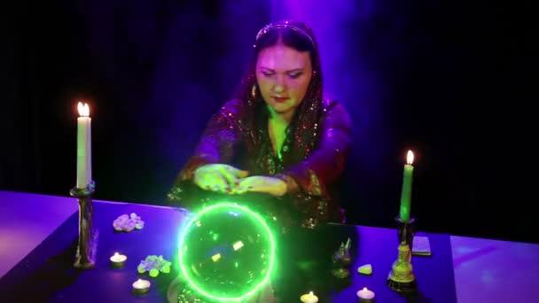 Cikánská věštkyně u stolu se zabývá magic s křišťálovou kouli, která svítí zeleně