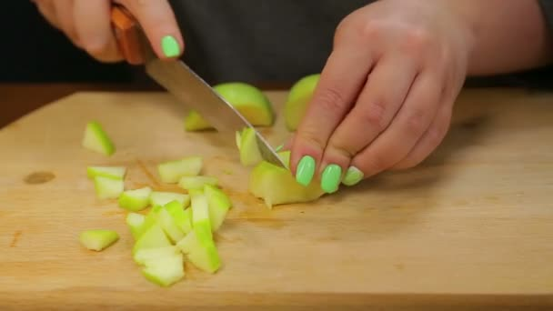 A woman cuts a green apple with a knife on a wooden board into small cubes.