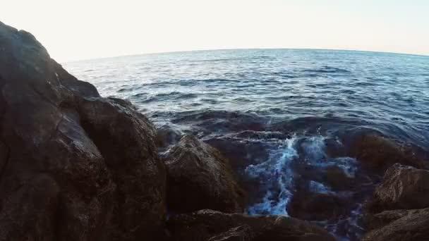 Skalnaté pobřeží a vlny, které narazilo kamenů na slunci večer