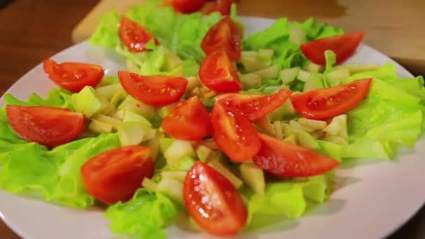 Ženská ruka klade plátky cherry rajčat v talíři se salátem